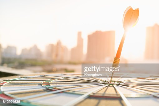Red dart arrow hitting in the target center of dartboard with modern city and sunset background. Target business, achieve and victory concept . : Stock Photo
