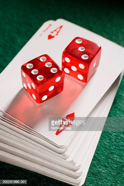 Red dice on pile of playing cards, close-up