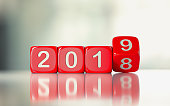 Red dices are rolling from 2018 to 2019. Numbers are engraved on dices. Dices are lit from the upper left corner of the composition and casting shadows over defocused background. New year and change c