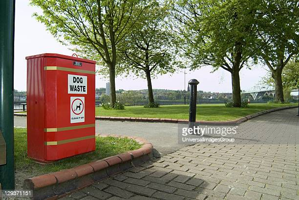 Red dog waste bin for responsible dog owners to deposit their pets excrement adjacent to childrens playground and leisure park by the banks of the...
