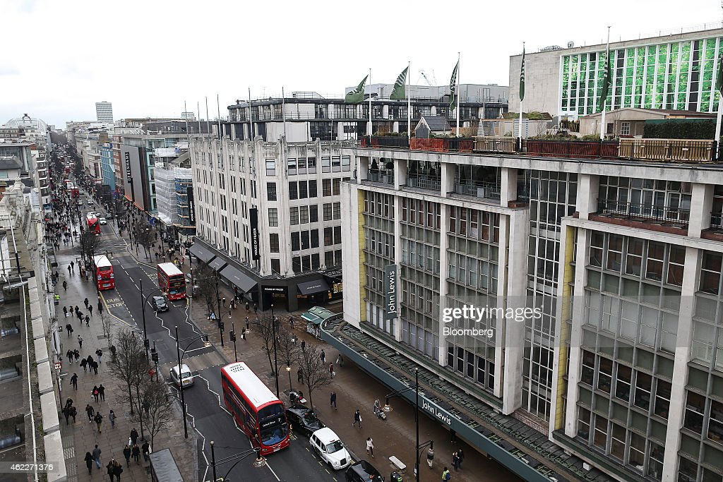 Red double deck buses London taxi cabs and pedestrians pass department stores operated by John Lewis Plc House of Fraser and Debenhams Plc on Oxford...