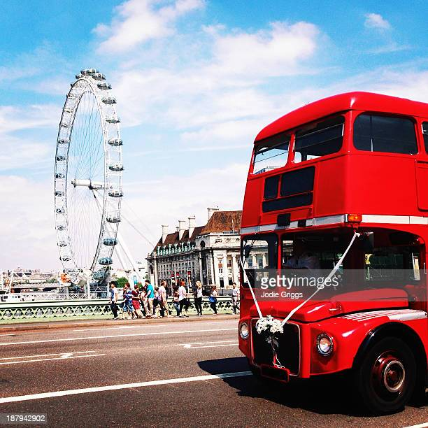 Red double decker bus driving passed London Eye