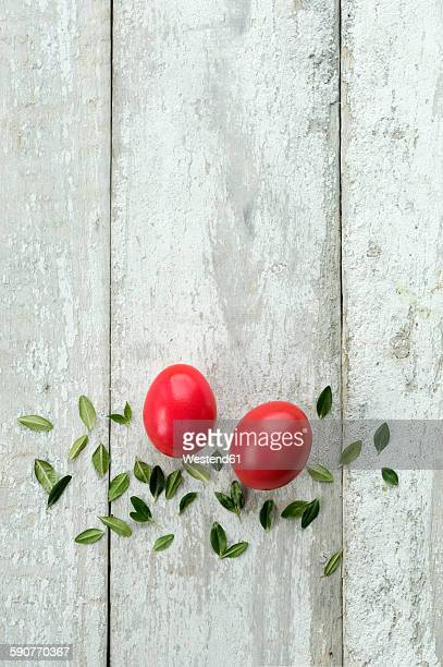 Red Easter eggs and leaves on wood