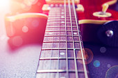 Red electric guitar close-up. Music concept. Vintage guitar on a background of sunlight and bokeh