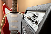 Red electric guitar plugged into large speaker. Close up of amplifier controls with blur effect on background. Playing guitar in home.