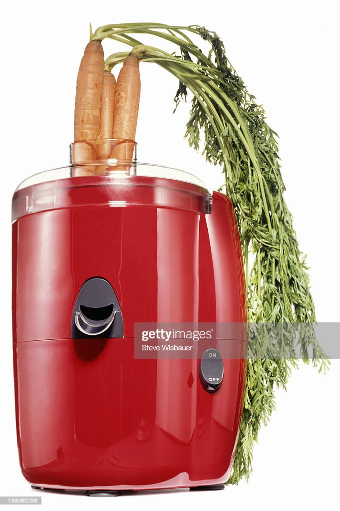 A red electric juicer with carrots : Stock Photo