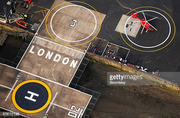 A red emergency air ambulance helicopter sits on the tarmac at London Heliport on the South Bank of the River Thames in this aerial photograph taken...