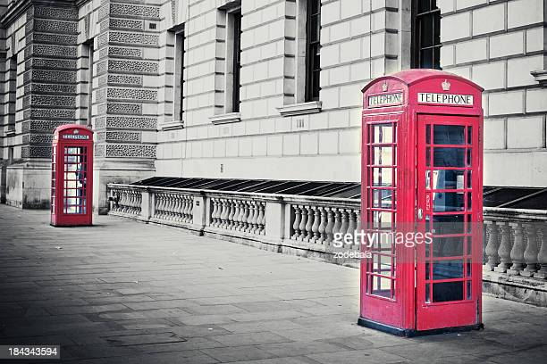 Red English phone booths in black and white photo