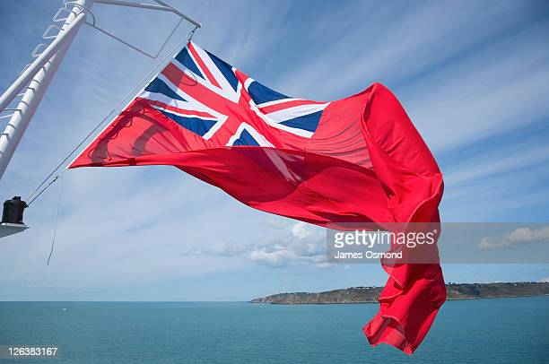 Red ensign flag blows in the wind on a ship sailing along the coastline.