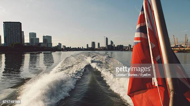 Red Ensign Flag On Nautical Vessel Sailing In Thames River Against Sky