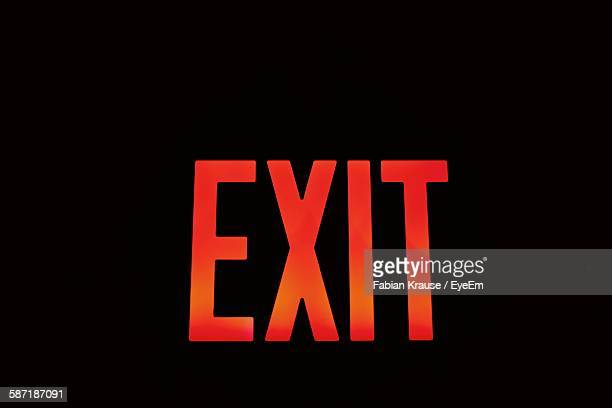 Red Exit Sign Against Black Background