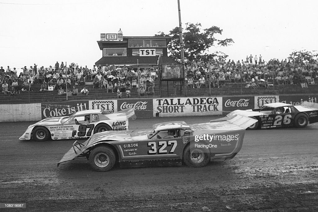 A Red Farmer crewman (No. F-97), Don Hester (No. 327) and Larry Spurlock (No. 26) take a slow lap in their Late Model dirt stock cars during warm-ups at the Talladega Short Track.