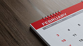 Red February 2019 calendar on brown reflective wood surface. Horizontal composition with copy space. Calendar and reminder concept with selective focus.