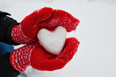 red female gloves hold a white heart from the snow. The concept of love and acceptance