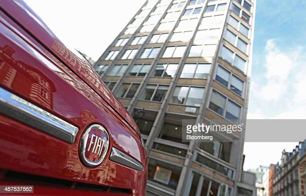 A red Fiat 500 automobile manufactured by Fiat SpA is seen parked outside the offices housing the new headquarters of Fiat Chrysler Automobiles NV...