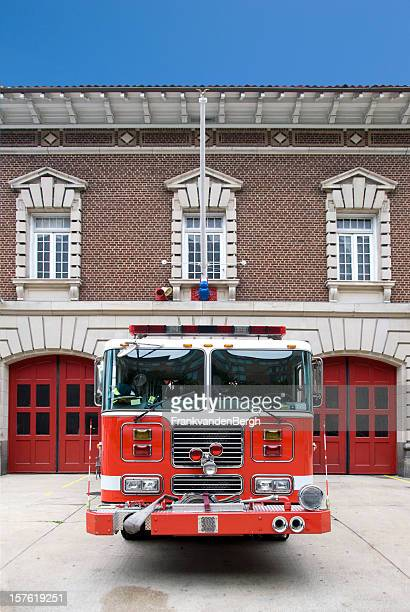 Red Fire Engine in front of  a Fire Station.