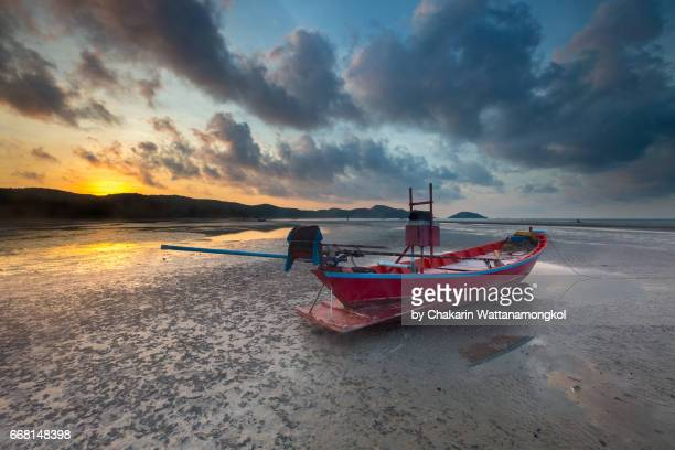Red fishing boat on the sand at low tide with sunrise sky.