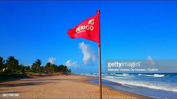 Red Flag At Flamengo Beach Against Blue Sky