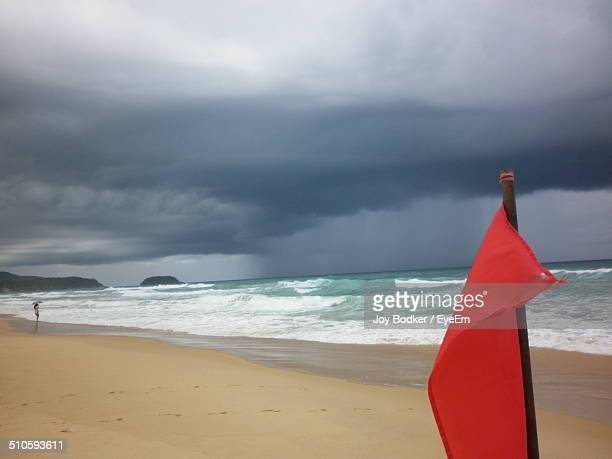 Red flag on beach against stormy cloud