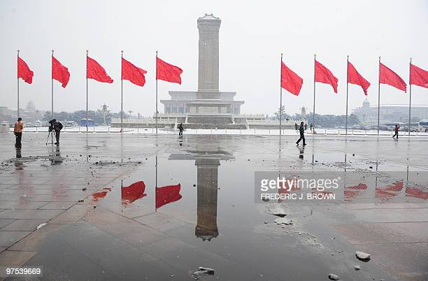 Red flags and the Monument to the People's Heroes are reflected in snowmelt on Tiananmen Square while delegates attend a session of the ongoing...