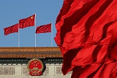Red flags flutter in the wind near the Chinese national emblem outside the Great Hall of the People where sessions of the Chinese People's Political...