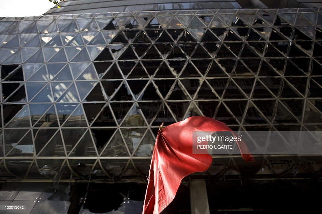 A red flags hangs in front of Thailand's biggest shopping mall - Central World - after it was set ablaze the day before following an army assault on an anti-government protest site in downtown Bangkok on May 20, 2010. Thai troops hunted for militant protesters who left parts of Bangkok in flames as the authorities extended a night curfew in the capital despite tentative signs of a return to normality.