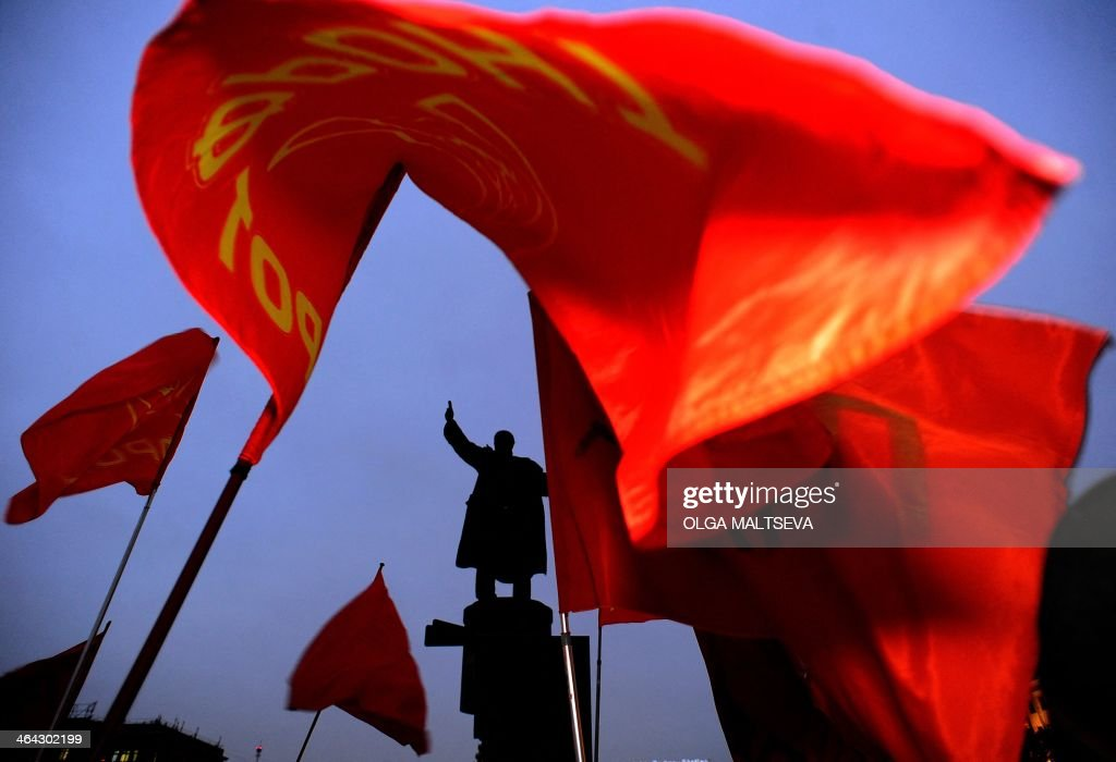 Red flags of Russian Communists fly near a monument to the Soviet Union founder Vladimir Lenin during a rally to mark the 90th anniversary of his...