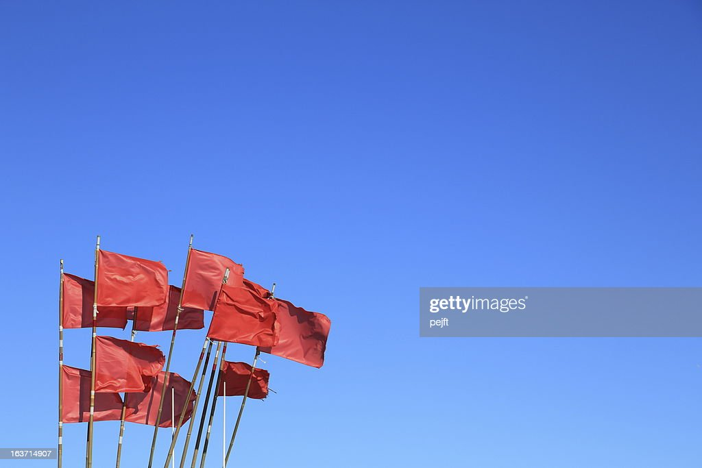 Red flags on blue sky : Stock Photo