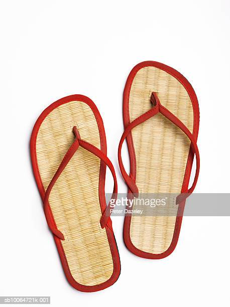 Red flip-flops with straw soles, close-up, studio shot