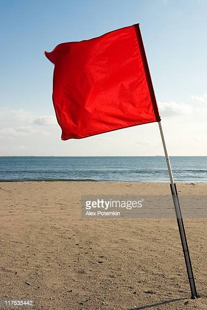 Red flying flag on the beach