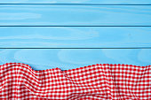 Red folded tablecloth over blue wooden table. Top view