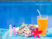 Red frangipani (plumeria) flowers, sungrasses, shampoo, lotion, hat, rolled up towels and Orange juice with a piece of lemon at the side of swimming pool. Vacation, beach, summer travel concept