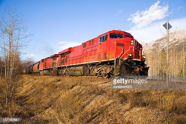 Red freight train traveling through dry landscape
