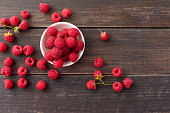Red fresh raspberries on brown rustic wood background. Bowl with natural ripe organic berries with peduncles on wooden table, top view with copy space