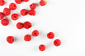 Red fresh raspberries on white background. Scattered natural ripe organic berries top view
