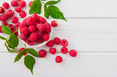 Red fresh raspberries on white rustic wood background. Bowl with natural ripe organic berries with peduncles and green leaves on wooden table, top view with copy space