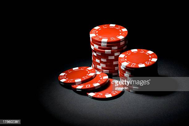 Red gaming chips in a spotlight on black background
