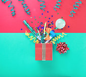 Red gift box with various party confetti, balloons, streamers, noisemakers and decoration on a multicolored background. Top view