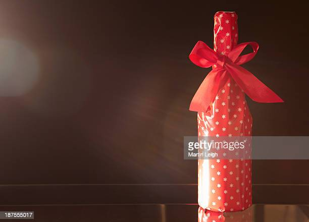 red gift wrapped champagne bottle with red bow