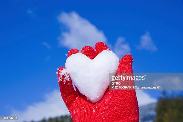 Red gloved hand holding heart made of snow