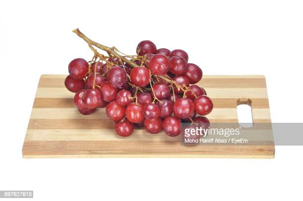 Red Grapes On Cutting Board Against White Background