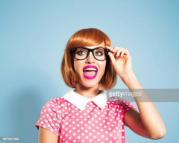 Red hair young woman wearing polka dot dress and glasses