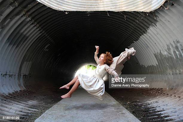 Red haired girl floating in tunnel