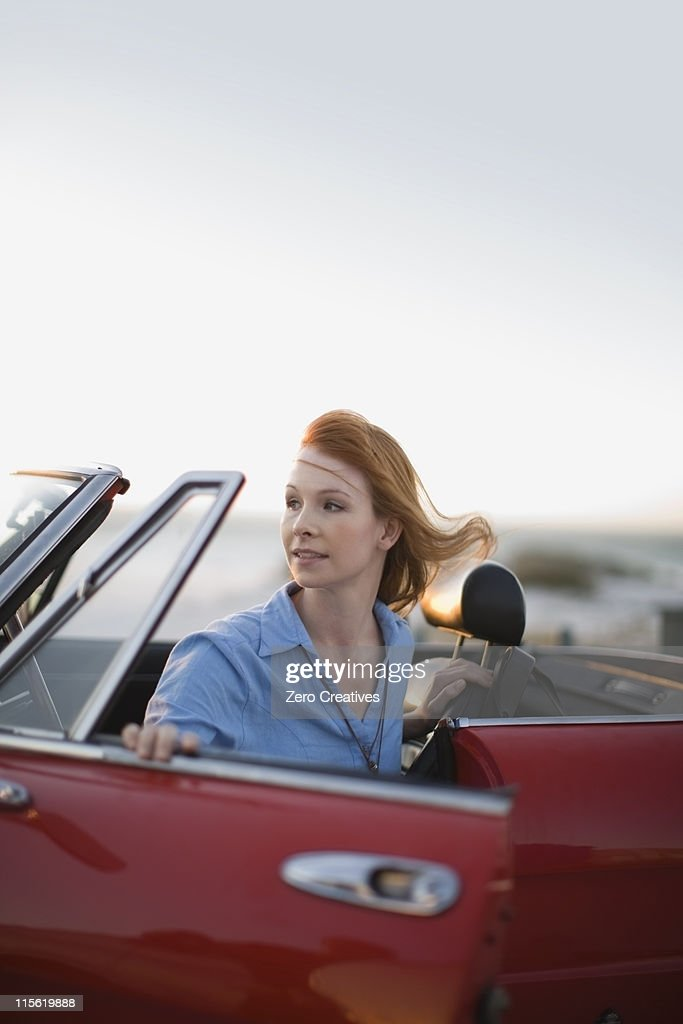 Red haired girl sittin in red car : Stock Photo