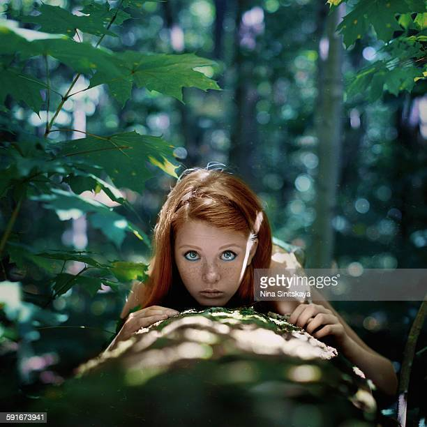 Red haired girl with big beautiful eyes in nature