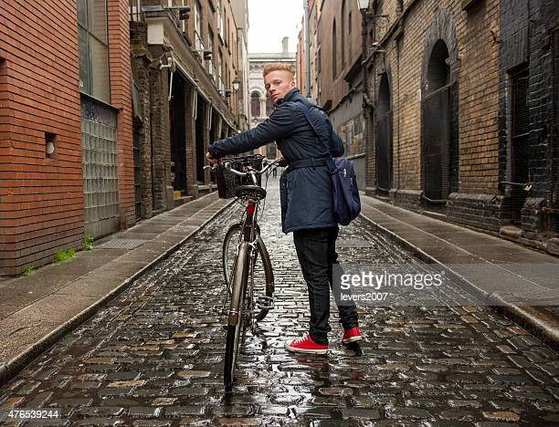 Red haired man walking in the city with his bicycle.