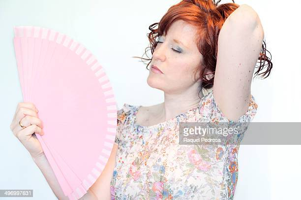 Red haired woman fanning herself