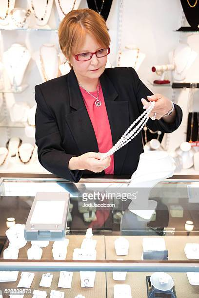 Red haired woman jewelry store owner displays a pearl necklace