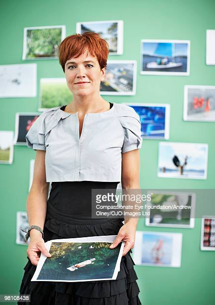 red haired woman standing in front of photos