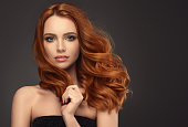 Young red haired woman  with voluminous, shiny and wavy hair . Beautiful model with long, dense and curly hairstyle. Flying hair.